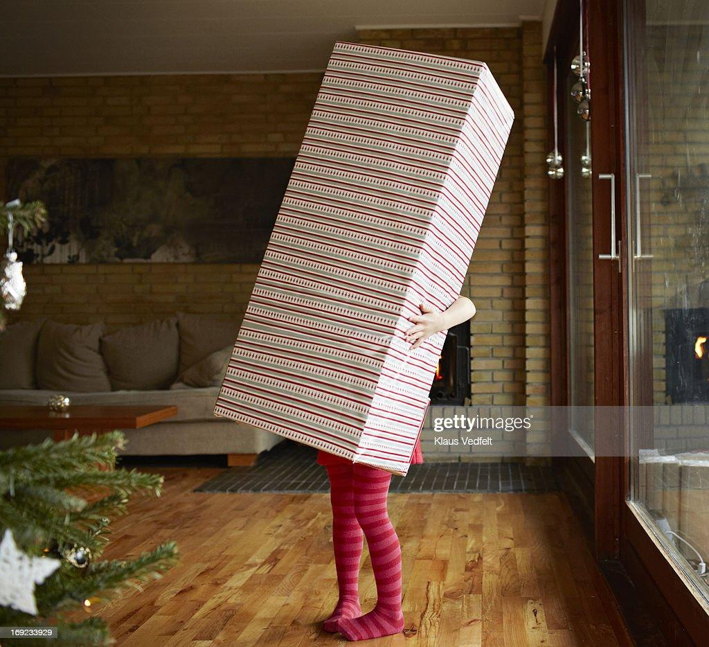 Little girl holding huge present : Stock Photo