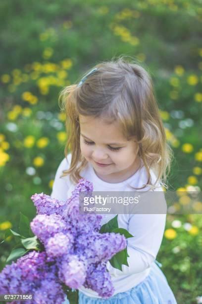 Kleine Mädchen Holding lila Blumenstrauß