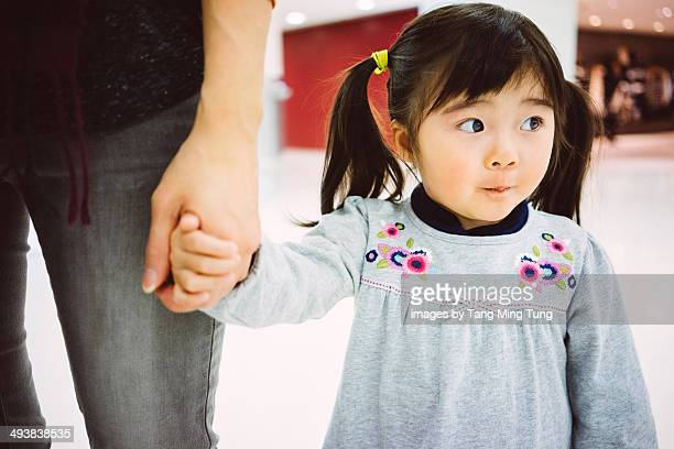 Little girl holding mom's hand strolling in mall