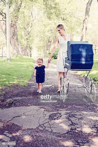 """kleines mädchen mit mutter hand gehen mit vintage-kinderwagen. - """"martine doucet"""" or martinedoucet stock-fotos und bilder"""