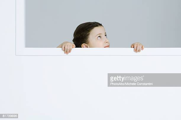 Little girl holding onto windowsill, looking up