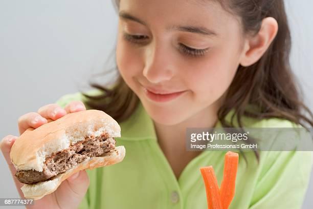 Little girl holding partly-eaten hamburger & carrot sticks