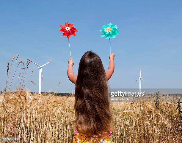 Little Girl holding pinwheels in front of Wind turbine countryside