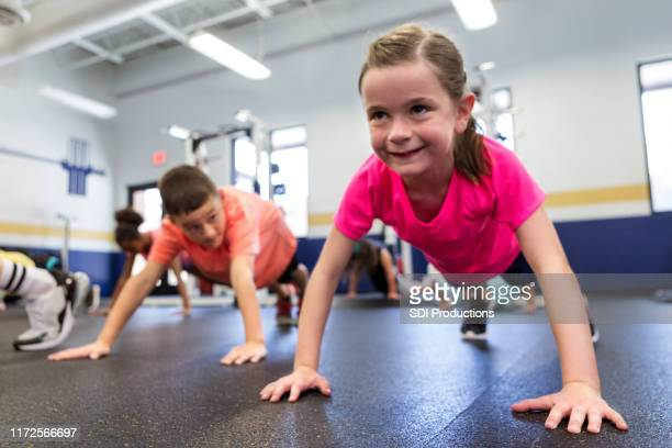 little girl holding plank position - physical education stock pictures, royalty-free photos & images