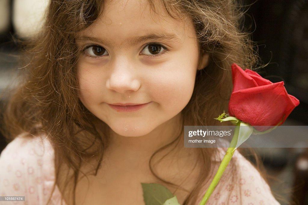 Little girl holding red rose : Foto de stock