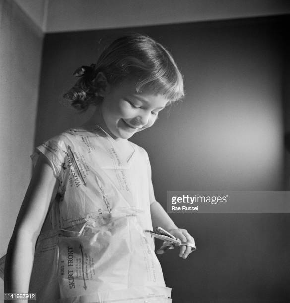 A little girl holding scissors gets her 'dream' dress handmade and tailored by a dressmaker at a McCall Pattern Company shop US circa 1950