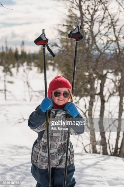 Little girl holding ski poles