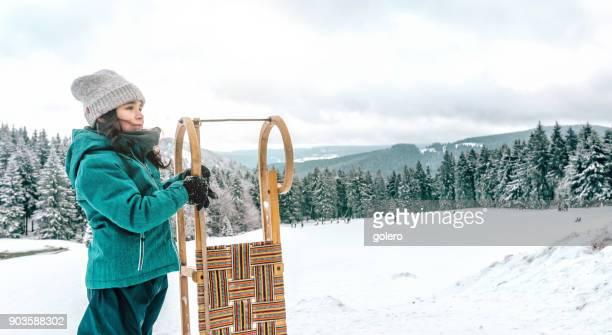 kleines Mädchen hält Schlitten im Winterlandschaft des Thüringer Waldes