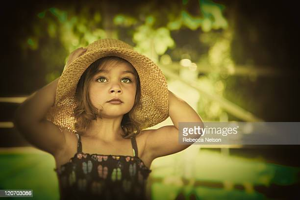 little girl holding straw hat on head - rebecca nelson stock pictures, royalty-free photos & images