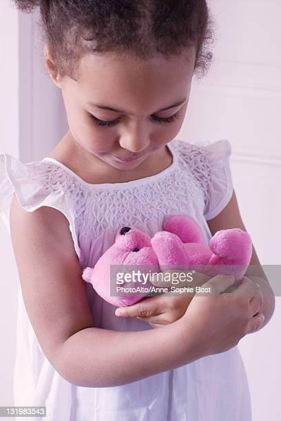 Little girl holding teddy bear affectionately