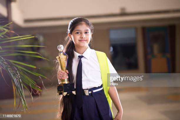 little girl holding trophy at school campus - schoolgirl stock pictures, royalty-free photos & images