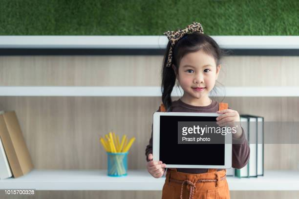 little girl holding up a blank tablet computer in classroom at school. education and technology concept. - very young thai girls stock photos and pictures