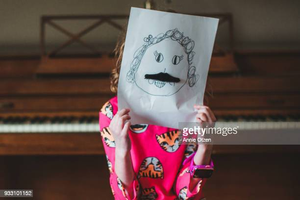 Little girl holding up a self portrait wearing a mustache
