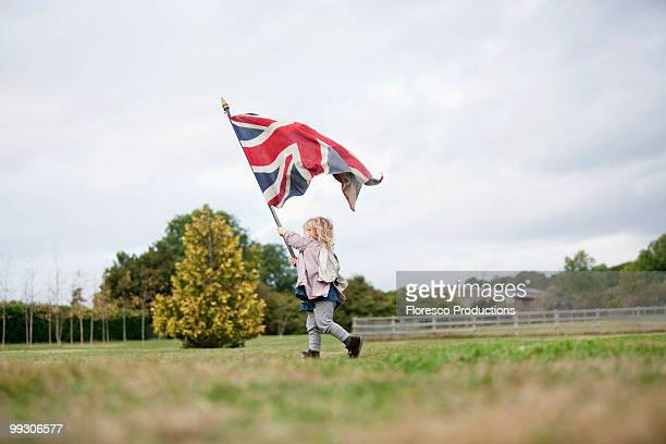 little girl holding up flag - union jack stock photos and pictures