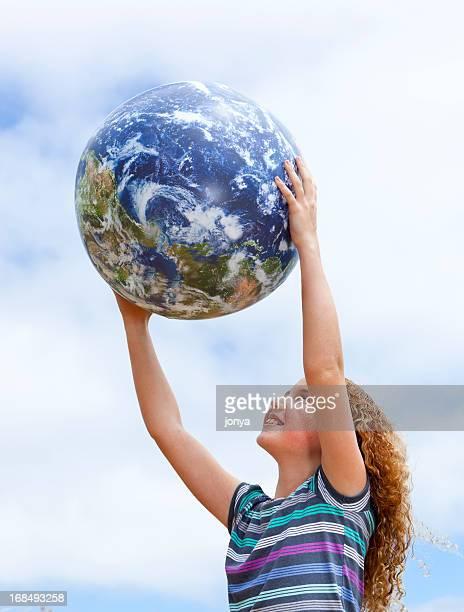 little girl holding up globe