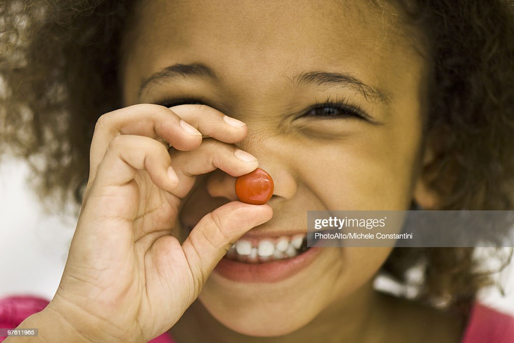 Little girl holding up piece of candy : Stock Photo