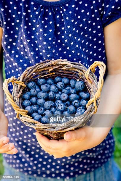 Little girl holding wickerbasket of blueberries
