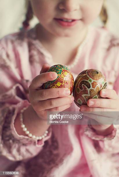 Little girl holding wooden eggs