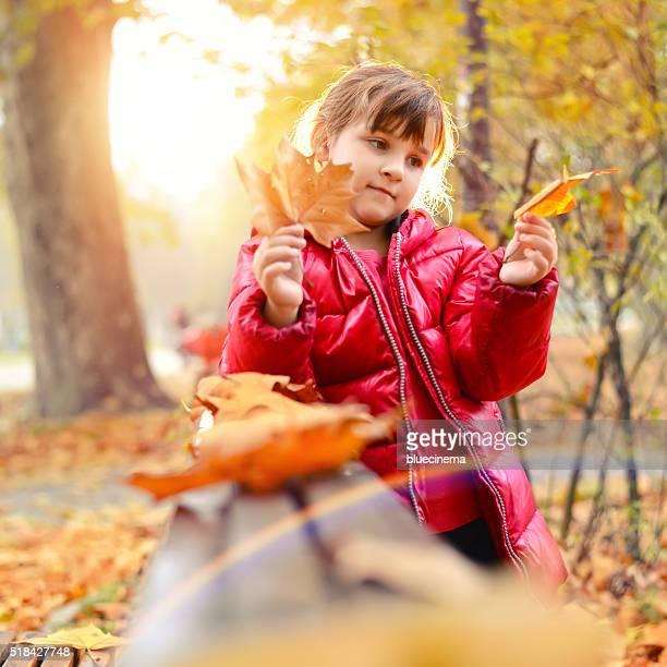 Kleine Mädchen Holding gelbe Ahorn Blätter