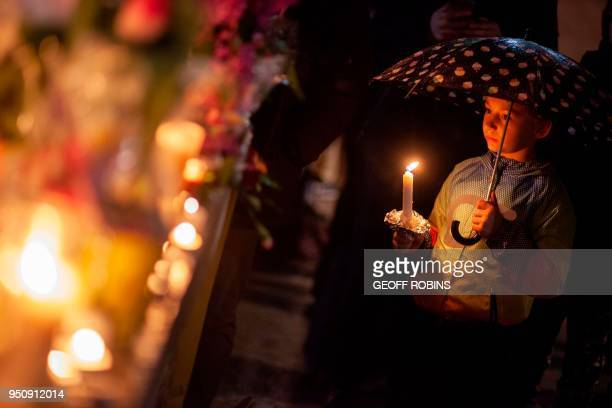 TOPSHOT A little girl holds a candle during a vigil on April 24 2018 in Toronto Canada near the site of a deadly street van attack A van driver who...