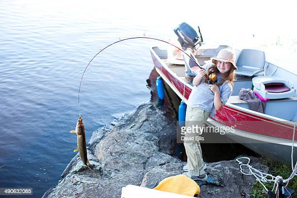 A little girl holds a fishing pole with a large fish on the end of the fishing line with the boat in the background.