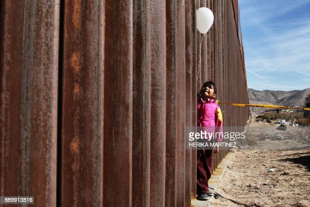 TOPSHOT A little girl holds a white ballon at the border wall between Mexico and the United States during the 'Keep our dream alive' event in Ciudad...