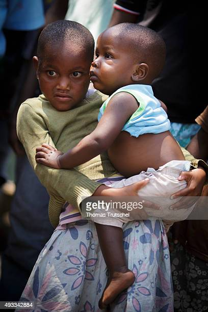 A little girl holds an infant in her arms and stands in a slum in the city area Beira on September 28 2015 in Beira Mozambique