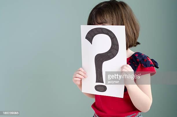 Petite fille détient un signe de Point d'interrogation