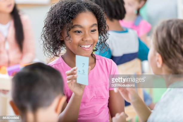 Little girl holds up mathematics flash card to quiz friend