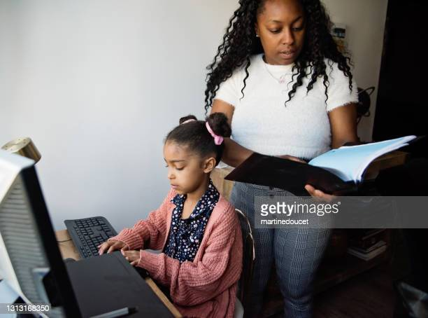 """little girl homeschooling on the family desk computer with mother's help. - """"martine doucet"""" or martinedoucet stock pictures, royalty-free photos & images"""