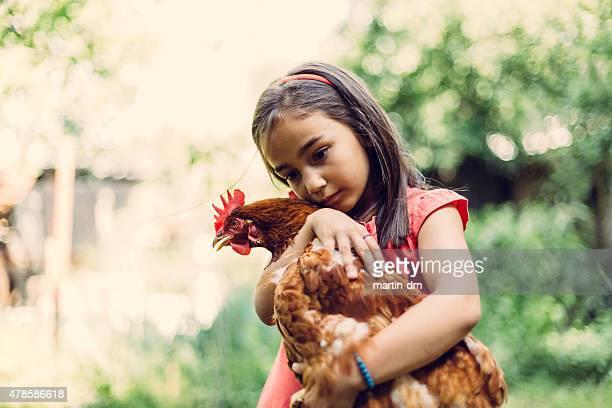 Kleines Mädchen umarmen eine hen