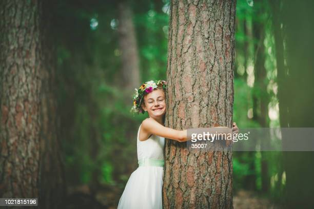 little girl hugging a tree - tree hugging stock pictures, royalty-free photos & images