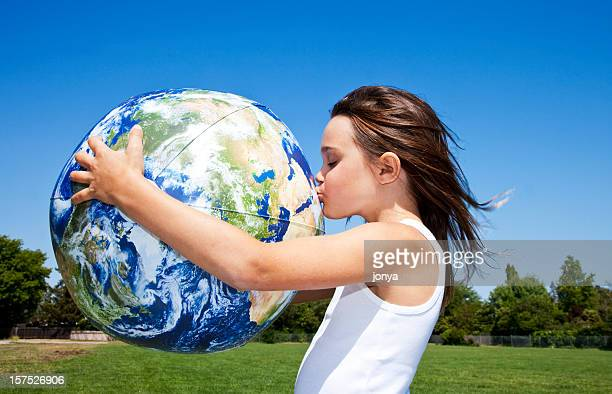 little girl hugging and kissing the globe