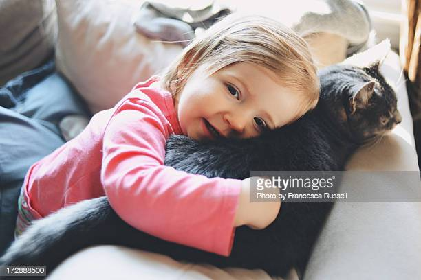 Little girl hugging cat.