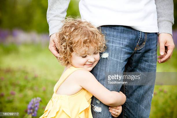Little girl hugging father's leg.