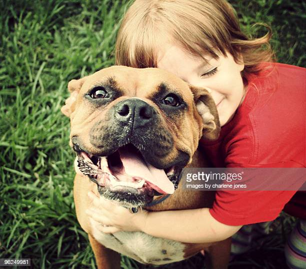 Little girl hugging happy dog