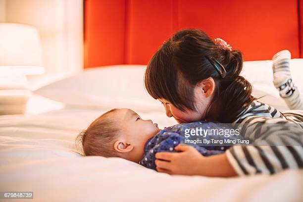Little girl hugging her baby sister on the bed