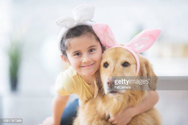 little girl hugging her easter dog - dog easter stock pictures, royalty-free photos & images