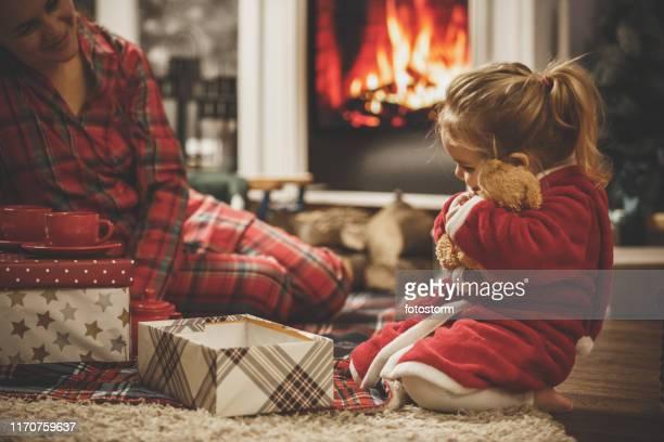 little girl hugging her new teddy bear on a christmas eve - christmas family stock pictures, royalty-free photos & images