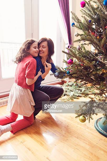 """little girl hugging mother decorating christmas tree. - """"martine doucet"""" or martinedoucet stock pictures, royalty-free photos & images"""