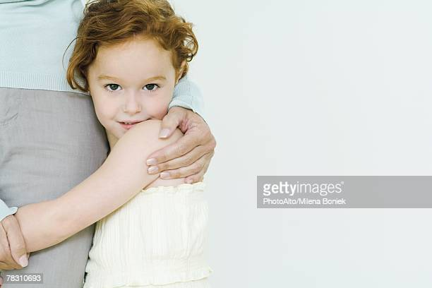 Little girl hugging mother's leg, looking at camera