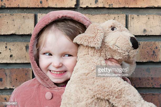 Little girl hugging stuffed dog, portrait