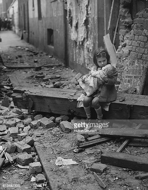 A little girl hugs her doll while sitting on a beam from her bombedout home in London England during the Blitz