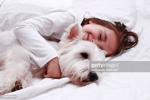 little girl hugs her white dog