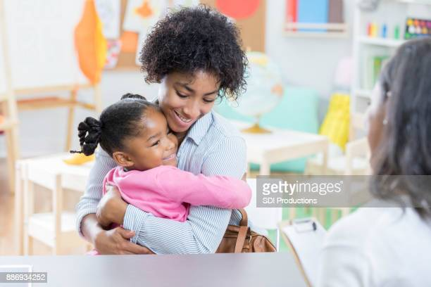 Little girl hugs mother during day care interview
