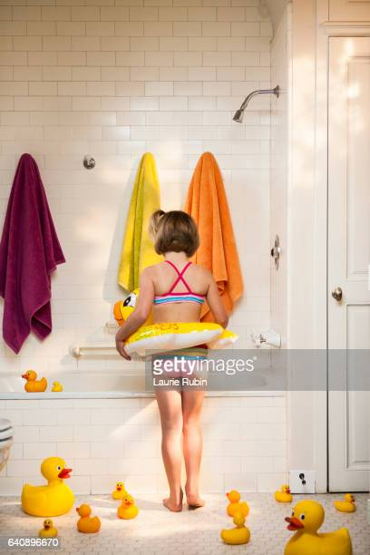 Little Girl in a bathing suit playing in a White  Vintage Bathtub,with colorful towels