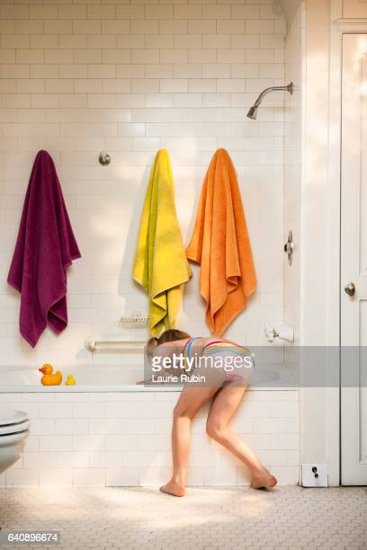 a little girl in a bathing suit playing in a white  vintage bathtub,with colorful towels - bending over stock pictures, royalty-free photos & images