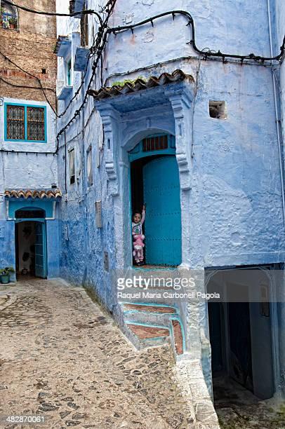 Little girl in a blue house doorway