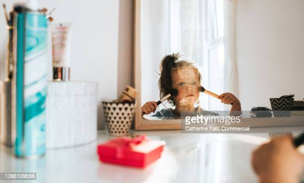 Little girl in a bright white bedroom, looking at her reflection in a mirror, and playing with make-up.
