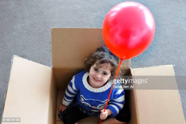 little girl in a cardboard box holding red balloon - rafael ben ari stock-fotos und bilder